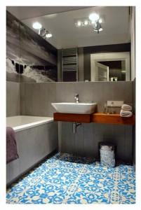 bagno appartamento progettato dal designer d'interni polacco Lucyna Kolodziejska . Il progettista ha decorato la casa in toni di grigio e una spruzzata di blu.a pav vecchie piastrelle marocc